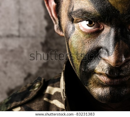 young soldier face looking straight ahead against a grunge wall - stock photo