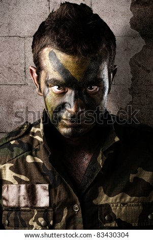 young soldier face looking straight ahead against a grunge wall