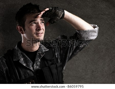 young soldier looking forward against a grunge wall