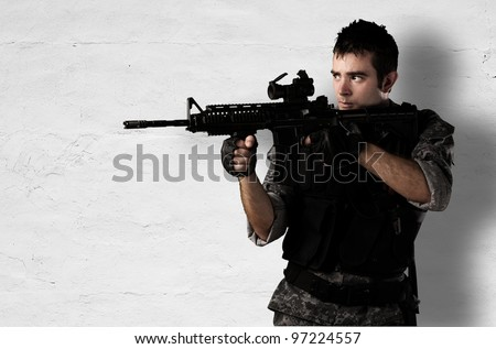 young soldier pointing with a rifle against a white wall