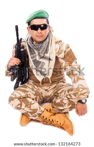 Young soldier with beret and glasses holding an automatic gun against white background