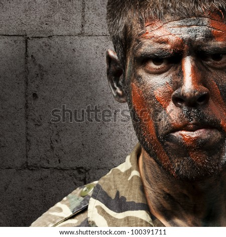 young soldier with camouflage paint looking very serious against a grunge bricks wall