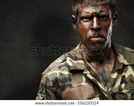 young soldier with camouflage paint looking very serious against a grunge wall