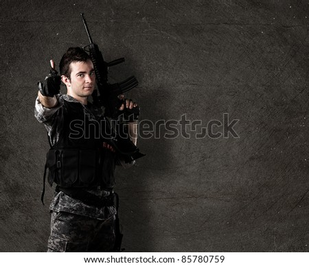 young soldier with rifle with finger up against a grunge wall - stock photo