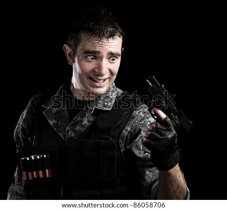 young soldier without ammunition of pistol on black background