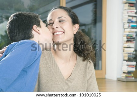 Young son kissing his mother on the cheek.