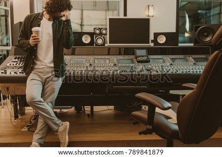 young sound producer standing at studio with cup of coffee to go #789841879