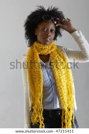 Young South African woman in jeans and yellow scarf lifting sunglasses off her face