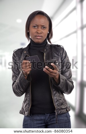 Young South African woman with a worried expression about her finances, holding a credit card, and doing a mobile phone transaction.