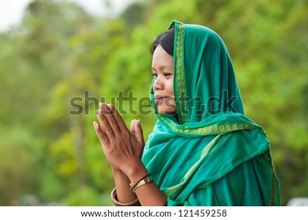 Young south-east asian woman praying with head dress