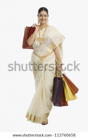 Young South Indian woman holding shopping bags and smiling
