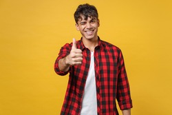 Young spanish latinos attractive handsome smiling stylish happy fashionable student man 20s wear red checkered shirt look camera show thumbs up gesture isolated on yellow background studio portrait