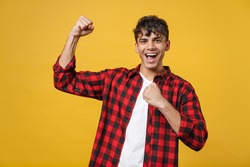 Young spanish latinos sporty fitness strong satisfied gladden man 20s wear red checkered shirt strong show biceps point index finger on muscles on hand isolated on yellow background studio portrait.