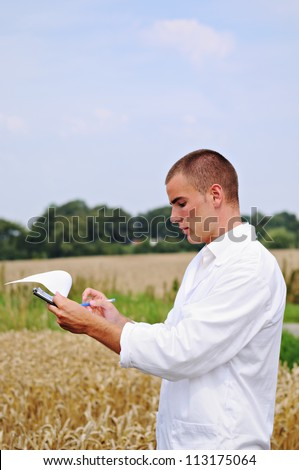 Young specialist checking results of his experiment in the wheat field