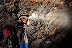 Young speleologist exploring a cave