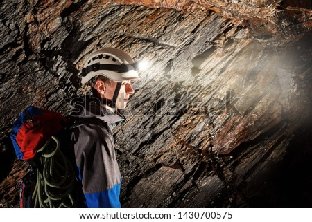 Young speleologist exploring a cave #1430700575