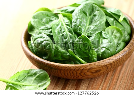 Young spinach in a wooden plate