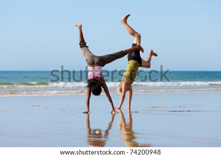 Young sport couple - Caucasian man and African-American woman � doing gymnastics on the beach
