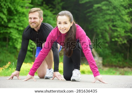 Young sport couple in starting position prepared to compete and run.