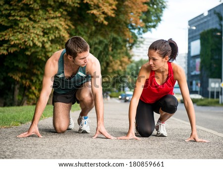 Young sport couple in starting postion prepared to compete, looking on each other