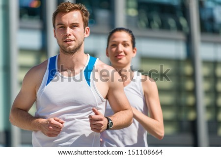 Young sport couple jogging in city environment - man first