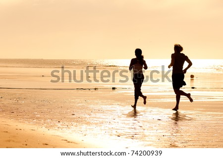 Young sport couple - jogging on the beach in sunset