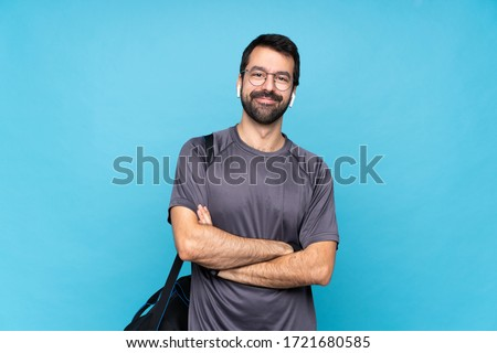 Young sport man with beard over isolated blue background with glasses and happy