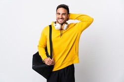 Young sport man with sport bag isolated on white background laughing