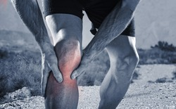 young sport man with strong athletic legs holding knee with his hands in pain after suffering muscle injury during a running workout training in trail desert dirt road in black and white