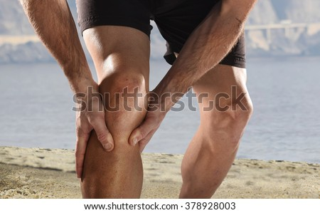 young sport man with strong athletic legs holding knee with his hands in pain after suffering muscle injury during a running workout beach training in muscular or ligament wound