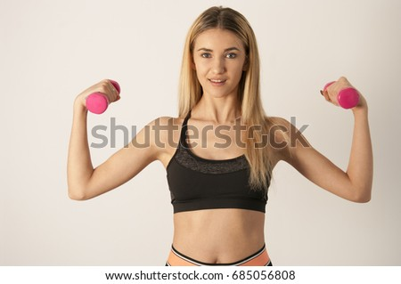 Young sport sexy fitness blonde woman posing on white wall in a tank top and leggings, sneakers #685056808