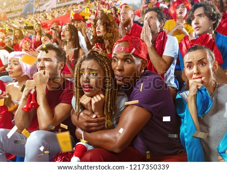 Young sport supporter fans at stadium. Tense moment in the game. Fans in anticipation during the match