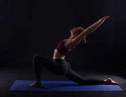 young sport woman doing yoga on mat over dark background