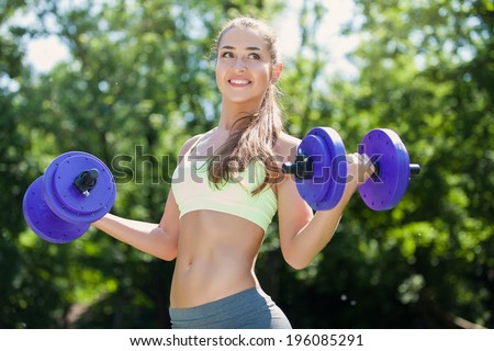 Young sport woman exercising with heavy steel dumbbell - outside in nature. Fitness exercise.