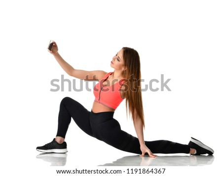 Young sport woman gymnastics doing stretching fitness exercise workout and make selfie on her cellphone isolated on a white background