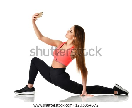 Young sport woman gymnastics doing stretching fitness exercise workout and make selfie on her cellphone mobile isolated on a white background