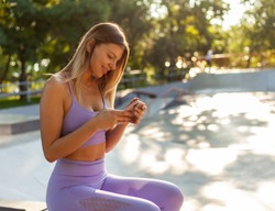 Young sport woman in sportswear is using a smartphone outdoors. Healthy lifestyle concept. Morning workout