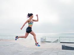Young sport woman in sportswear run on beach