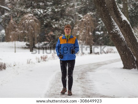 Young sport woman jogging during winter training outside in cold snow weather