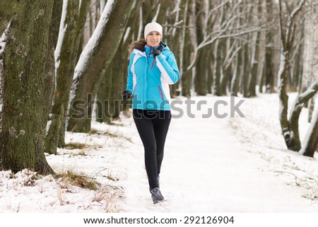 Young sport woman jogging in winter park. Sportswoman running on snowy pathway