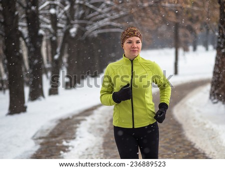 Young sport woman model  jogging during winter training outside in cold snow weather in park