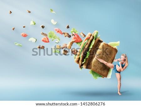 Young sport women boxing a hamburger as unhealthy food #1452806276