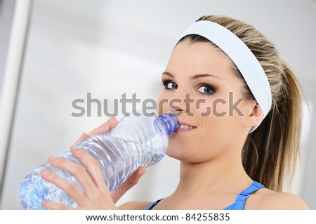 young sportive adult is drinking fresh water