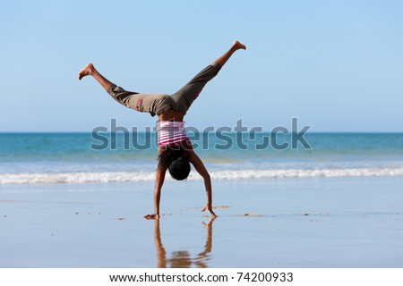 Young sportive African-American woman doing gymnastics on the beach