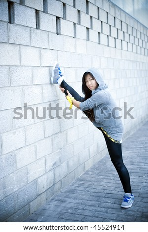 Young sportive asian girl stretching in urban background. - stock photo