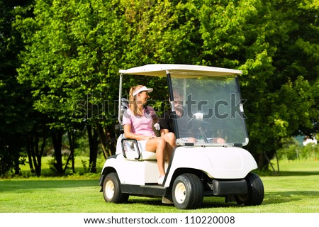 Young sportive couple playing golf on a golf course, they driving with golf cart