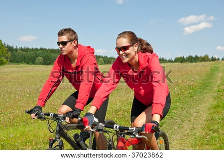 Young sportive couple riding mountain bike in spring meadow on a sunny day