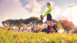 young sportive girl in uniform of rugby football player in a field. American football woman player in action holding a ball. Sport and lifestyle concept
