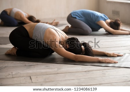 Young sportive girls practising together yoga positions at group session. Slim women lying resting on rubber mats doing Child Pose, calming the body, mind and spirit, stimulates the third eye point