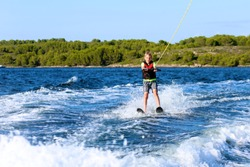 Young sportive teenage boy waterskiing from the boat. Adventurous summer holidays at the sea. Water sport activity on the beach.